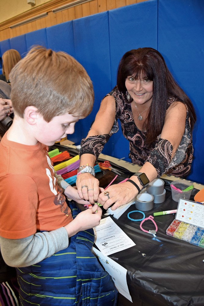 Wantagh Elementary School teacher Susan Berge assisted fourth-grade student Paul McHale with making an LED bracelet.