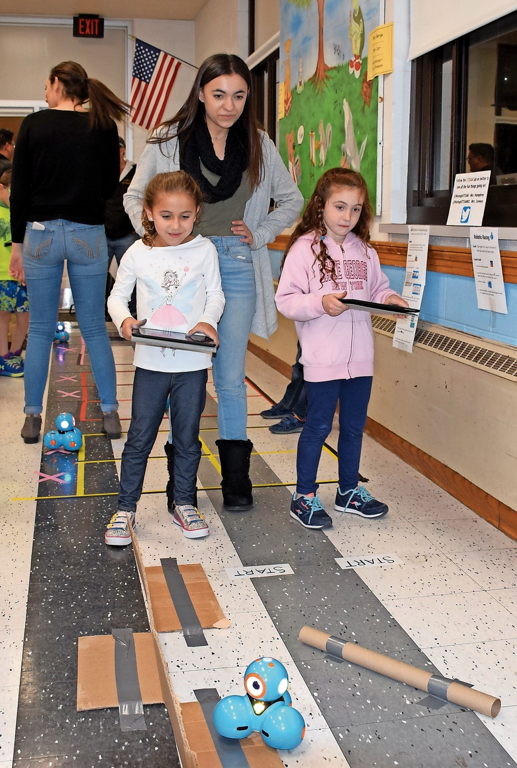 Hofstra University representative Jenna Alma assisted Wantagh Elementary School first-graders Julianna Lorenzotti, left, and Ella Tierney.