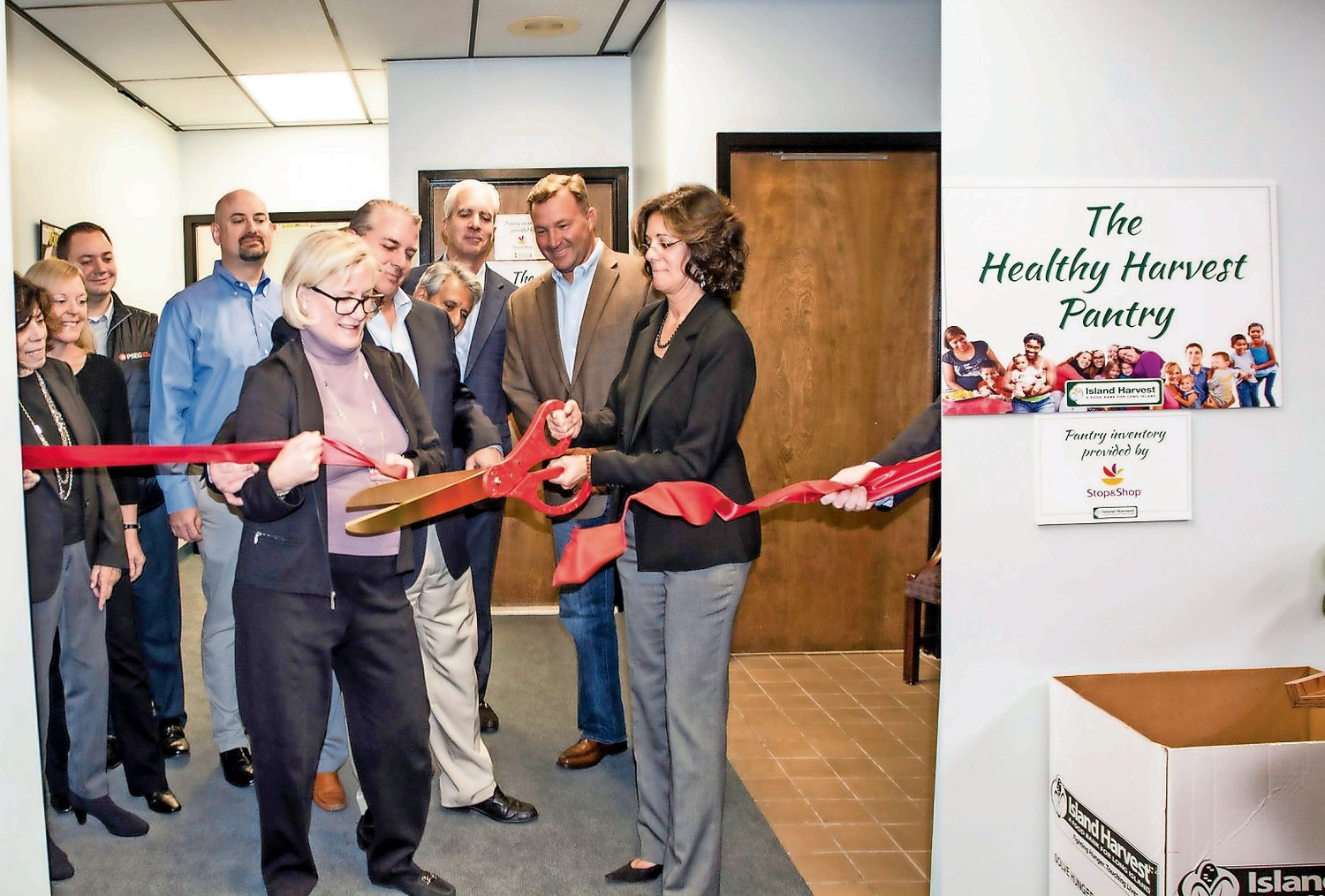 Cynthia G. Scott, executive director of The Safe Center LI, left, and Randi Shubin Dresner, president and CEO of Island Harvest Food Bank, cut the ribbon to officially open the Healthy Harvest Pantry in Bethpage, surrounded by board members of both organizations.