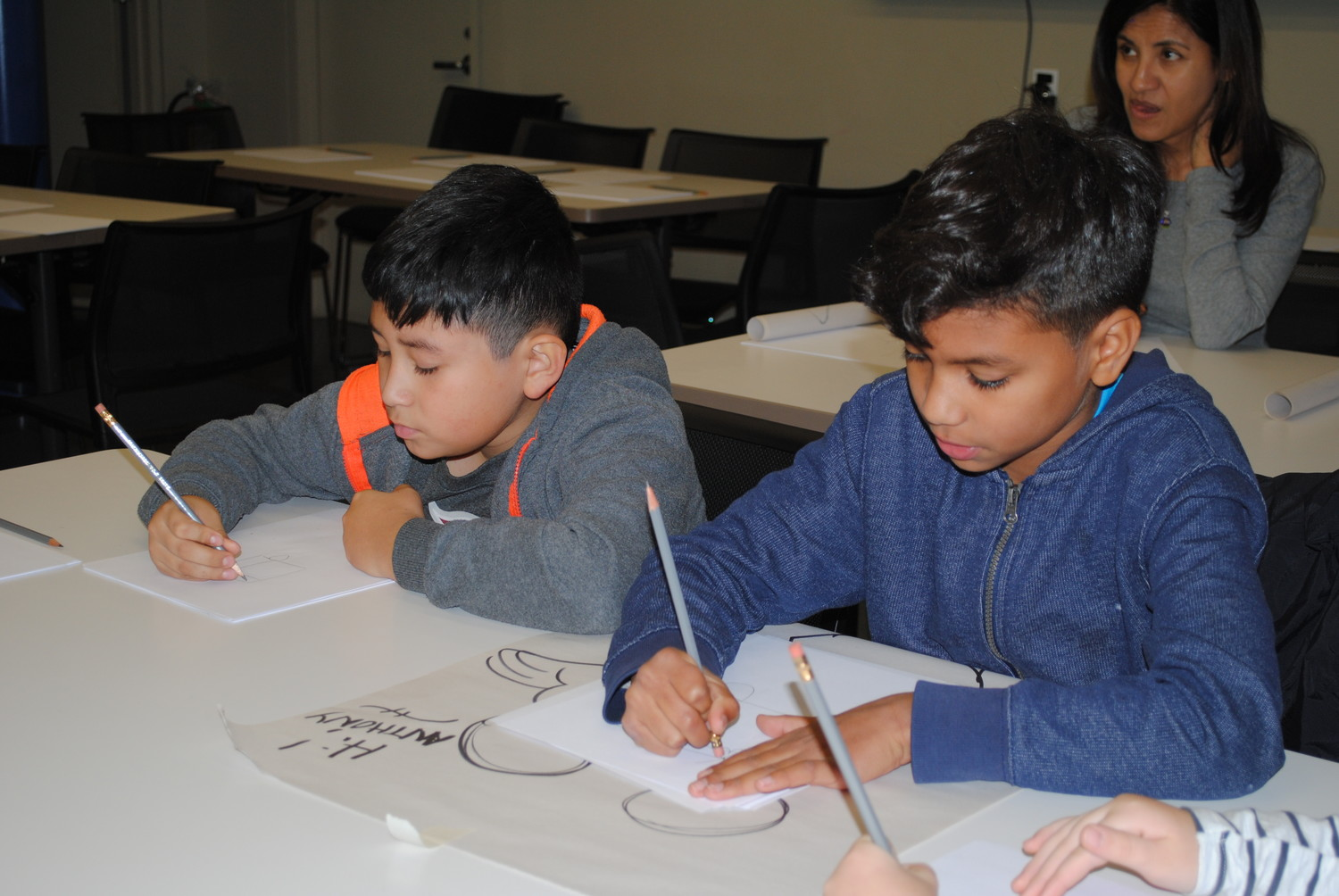 Bryant Reyes, 9, and Anthony Fernandez, 9, followed along with Ed Klein's instructions on how to draw Fred Flintstone.