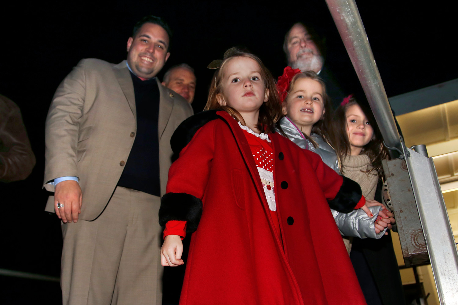Tessa Sanneman, in red, Kate Sanneman and Lila Rivara, alongside Hempstead Town Councilman Anthony D'Esposito, left, Trustee Emilio Grillo and Mayor Francis Murray, got ready to flip the switch too illuminate the village's Christmas tree.