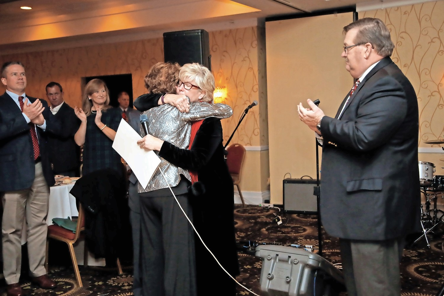 Village Mayor Patti Ann McDonald hugged Maier's wife, Maura Maier, at O.L.L.'s annual holiday gala.