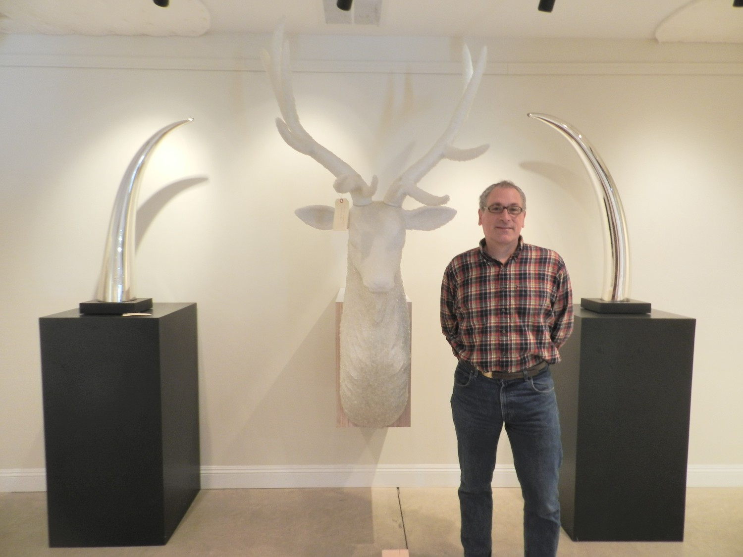 Locust Valley native and artist Joseph Rossano stood in the shadows of silvered tusks, which were constructed out of materials donated by the Museum of Glass.