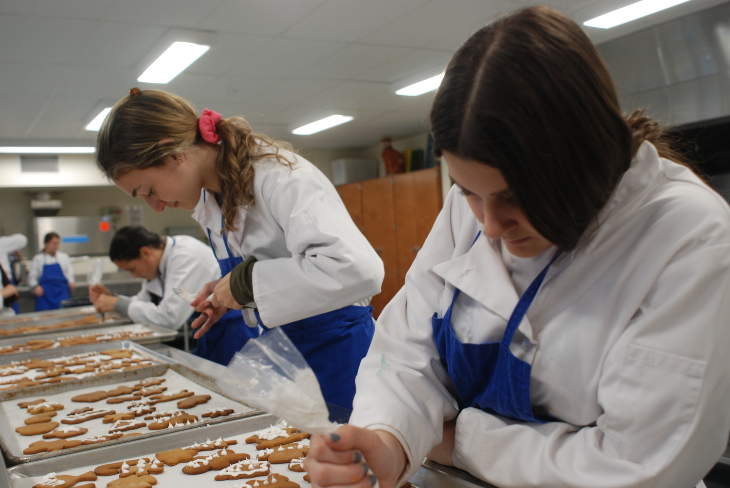 At Kennedy High School in Bellmore, 10th-graders Haylee Schwartz, left, and Sami Platt decorated gingerbread cookies as part of the Bellmore-Merrick Central School District's Culinary Arts and Hospitality Program.
