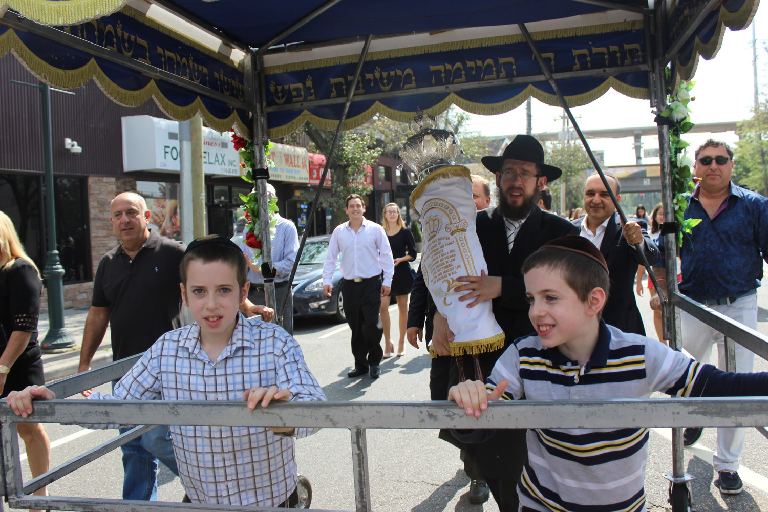 Rabbi Shimon Kramer, of the Chabad Center for Jewish Life in Merrick, marched up Merrick Avenue with his congregation's new Torah scroll when it was unveiled this fall. His sons Binyamin and Leibel, both 10, joined him.