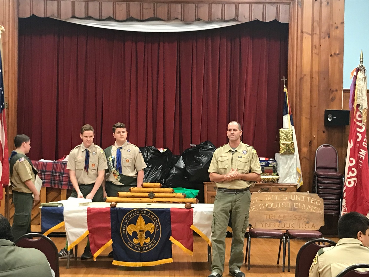 Steve Maroney said he didn't intend to become Troop 336's scoutmaster, but he cherishes the role. Above, he handed out badges to scouts at the quarterly Court of Honor ceremony at Saint James United Methodist Church in Lynbrook on Dec. 18.