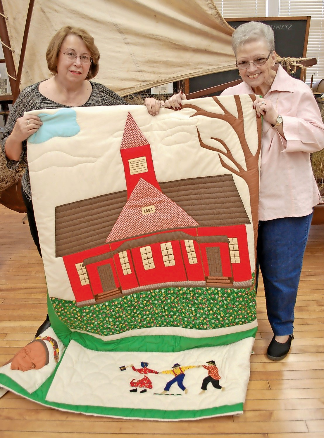 Bongiovi and past Chamber of Commerce President Carla Powell showed off a quilt made in the mid-1970s by 16 women in Seaford, depicting the former schoolhouse that now serves as the local history museum.