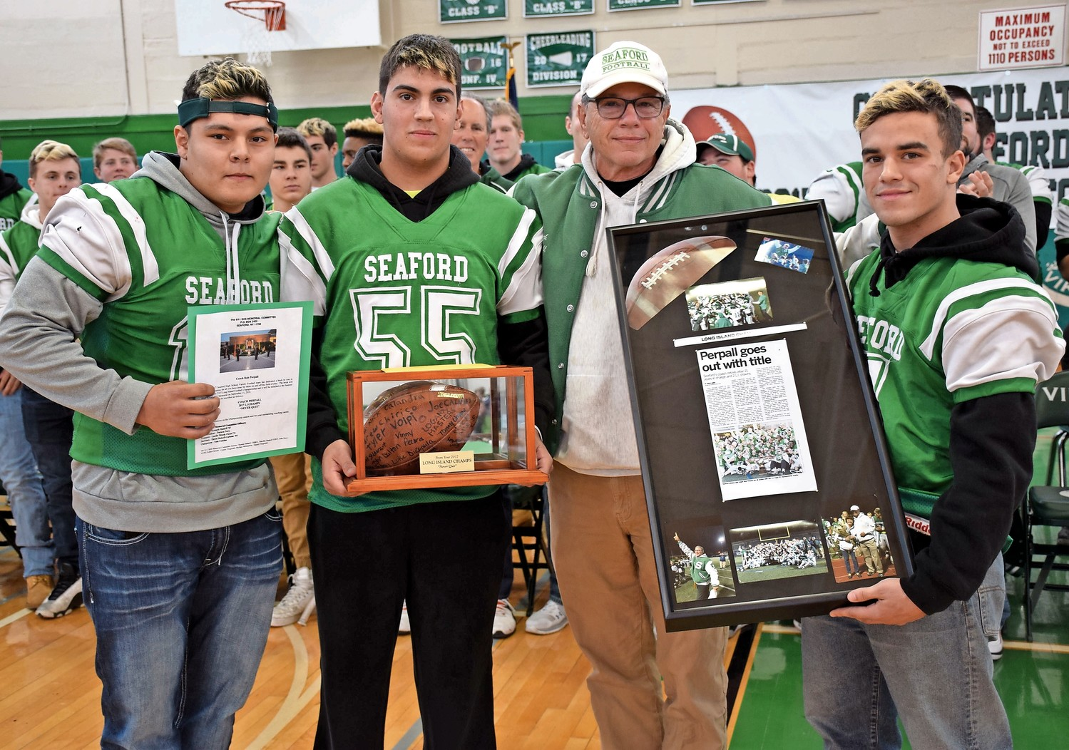 Seaford High School football captains Nicholas Calandra, far left, Andrew Chirico, second from left, and Tyler Volpi, right, presented gifts to retiring coach Robert Perpall, including a football signed by all of the team's players and a plaque commemorating the championship game.