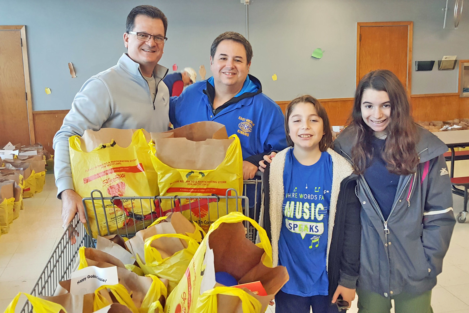 Distinguished kiwanis club of East Meadow Past President Harry Demiris, Jr., left, helped Ross Schiller and his children, David and Hailey, with holiday food baskets.
