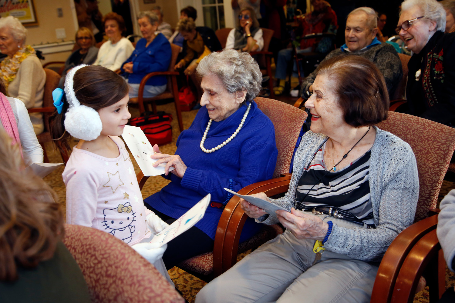 Rieley Cohen handed out holiday cards to seniors Ruth Miller and Cynthia Dorfman.