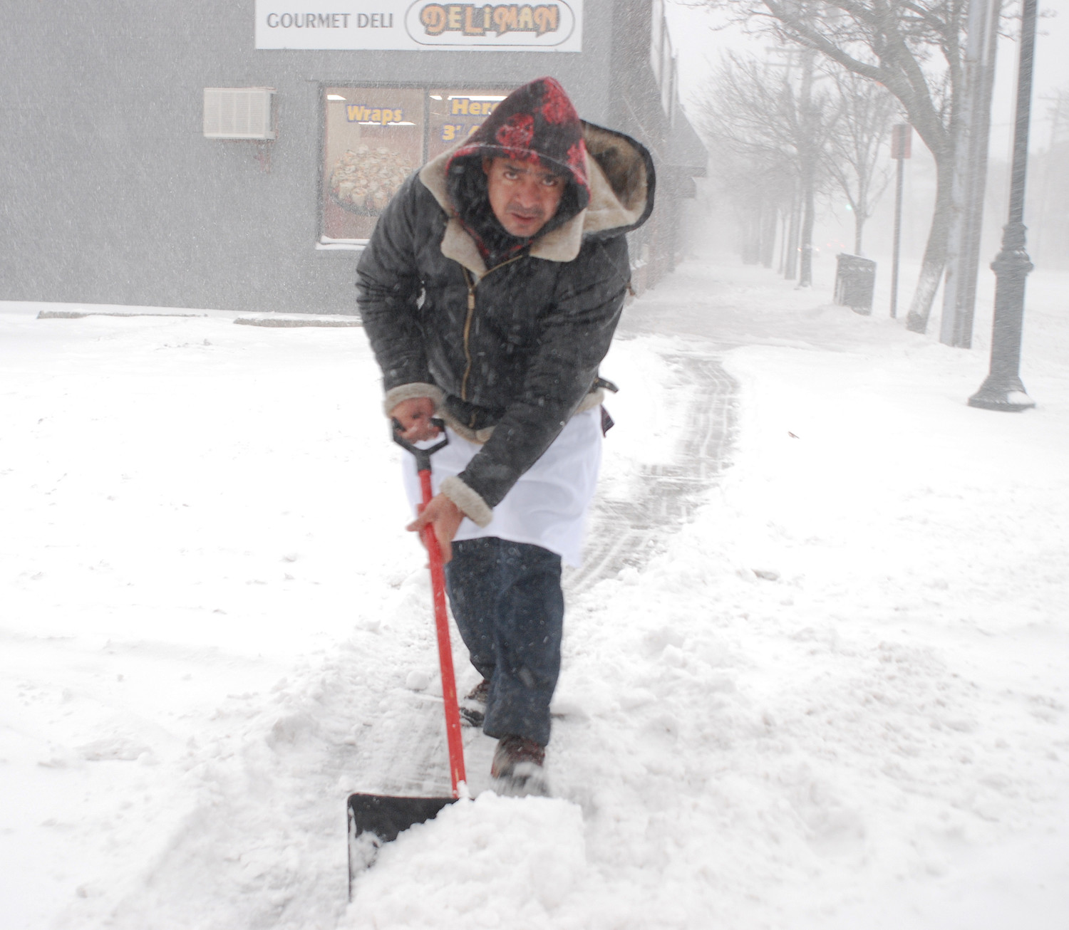 A worker, who did not wish to be identified, cleaned up a sidewalk in downtown Merrick around 8 a.m. Thursday.