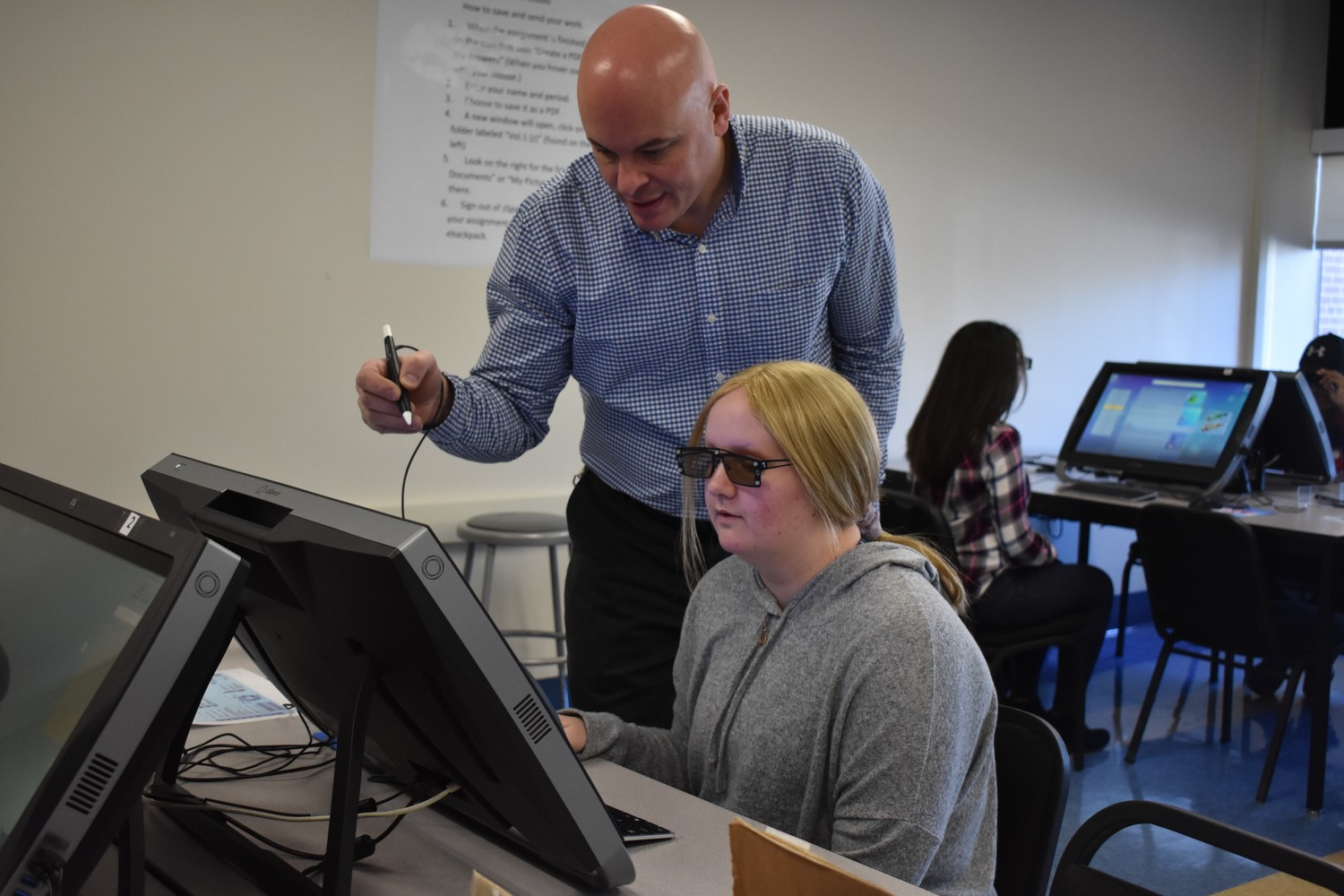 Chris D'Ambrosio, a science teacher at South Side High School, helped student Emma Garrett use one of the district's zSpace computers to analyze and label parts of the human body's circulatory, respiratory and digestive systems.