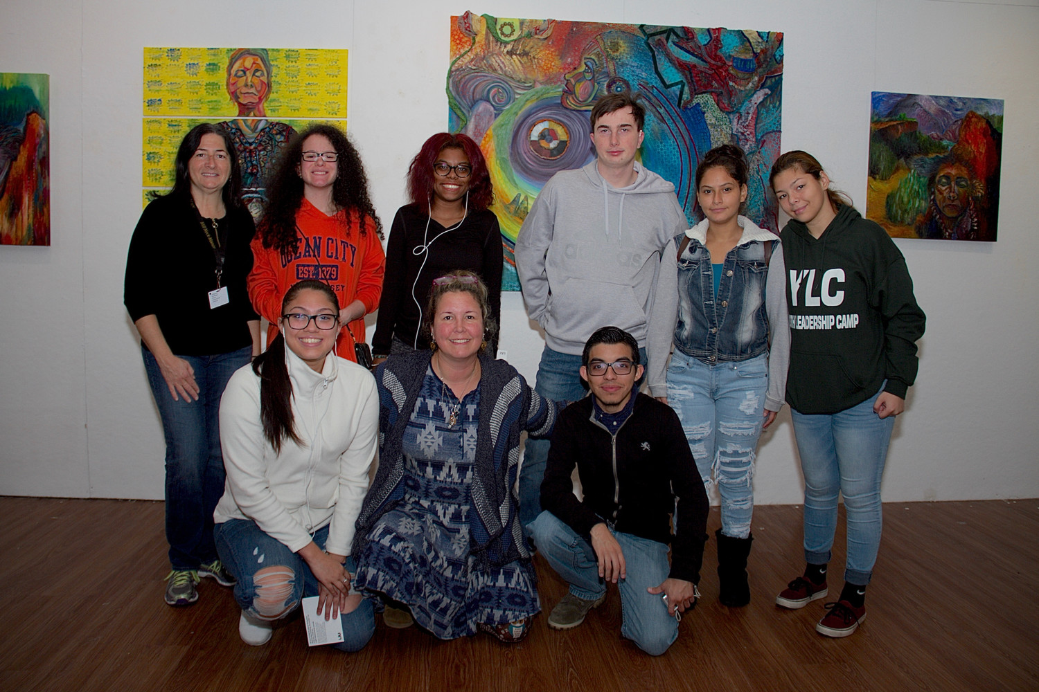 Artist Sharon Papp, kneeling, center, with Rebecca Pilson, a teacher assistant at Mill Neck, standing at far left, and students from the school at LIU Post's library gallery.