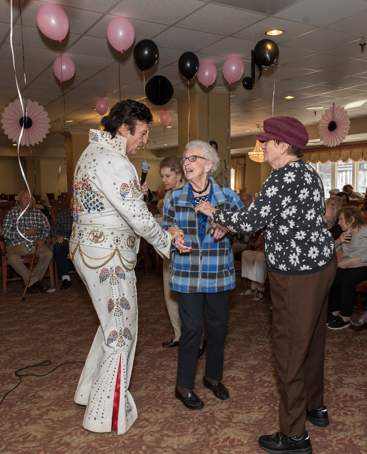 Irene Guardio, center, and Joyce Geurdes dance under a canopy of pink and black balloons with the King of rock 'n' roll.