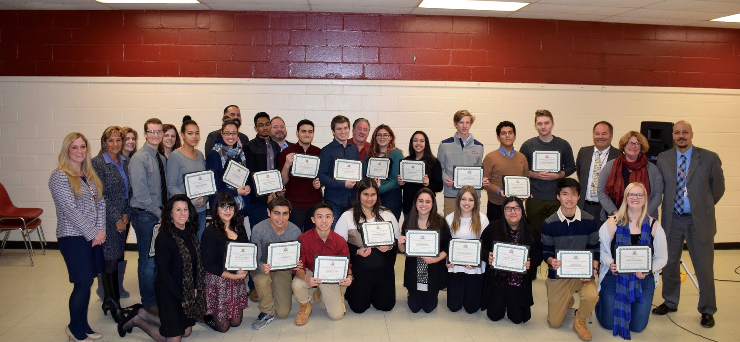 Current and former Glen Cove High School students receive certificates as Advanced Placement scholars.