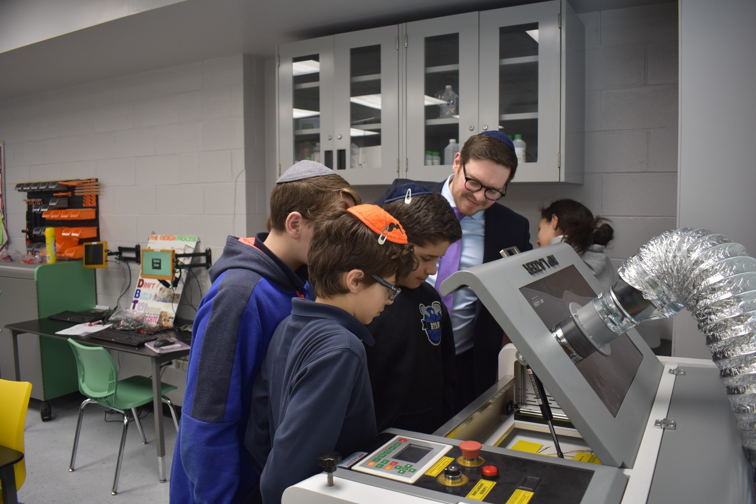 Middle School Principal Josh Gold and students, from left, Benny Krysman, Tommy Nandel and Corey Spitzer checked out the STEM lab's laser cutter.