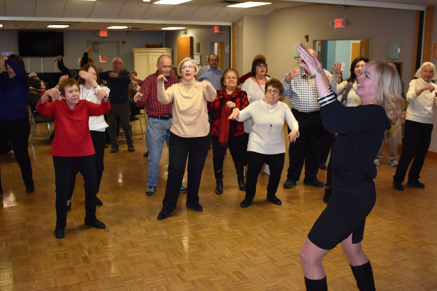 "Nancy Codispoti, right, deputy director of the village's department of senior services, led partygoers in a dance to Bruno Mars' ""Uptown Funk."""