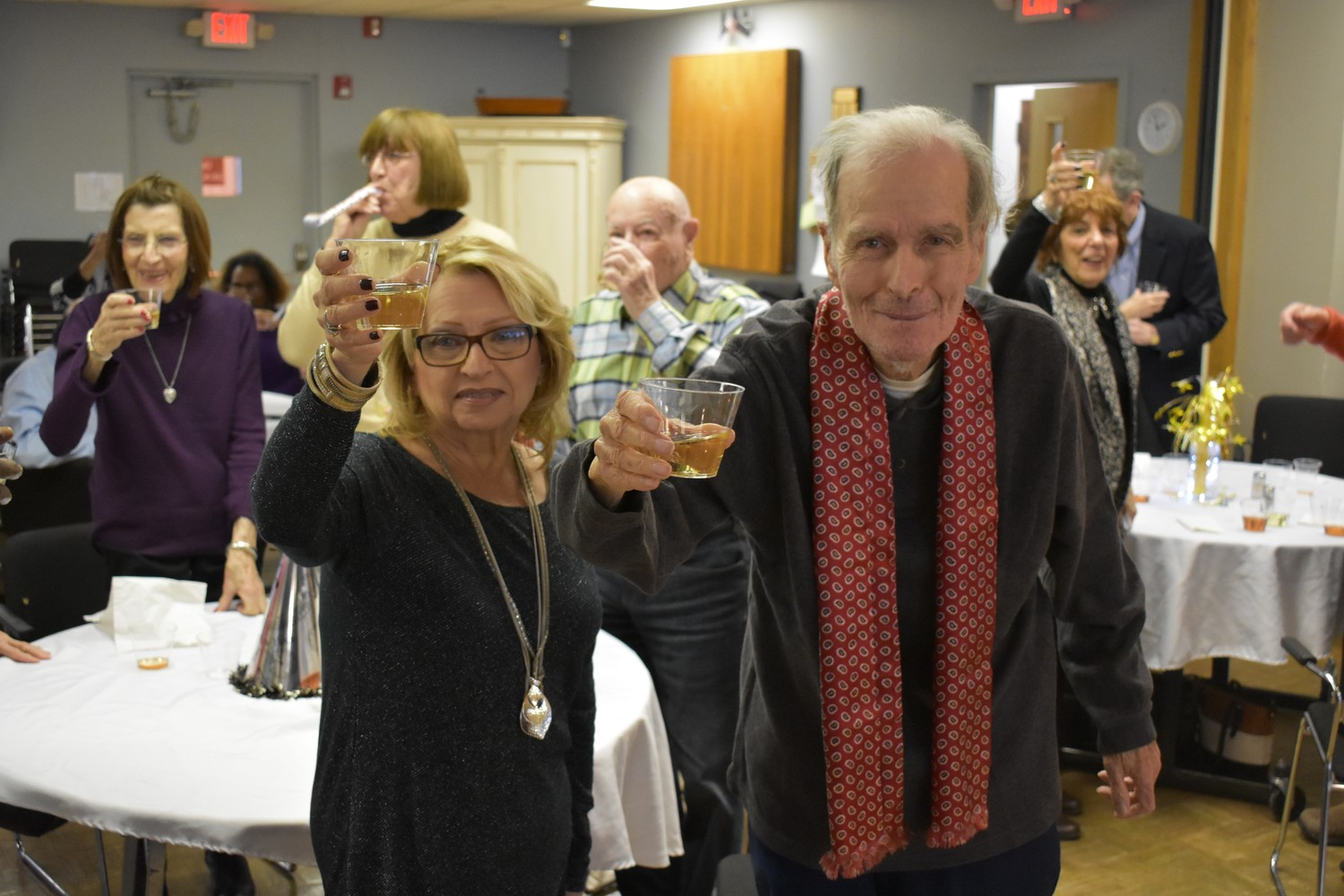 Lee Schmidt, left, and John Bones raised their glasses to celebrate the coming of 2018 during the center's annual New Year's party on Monday.