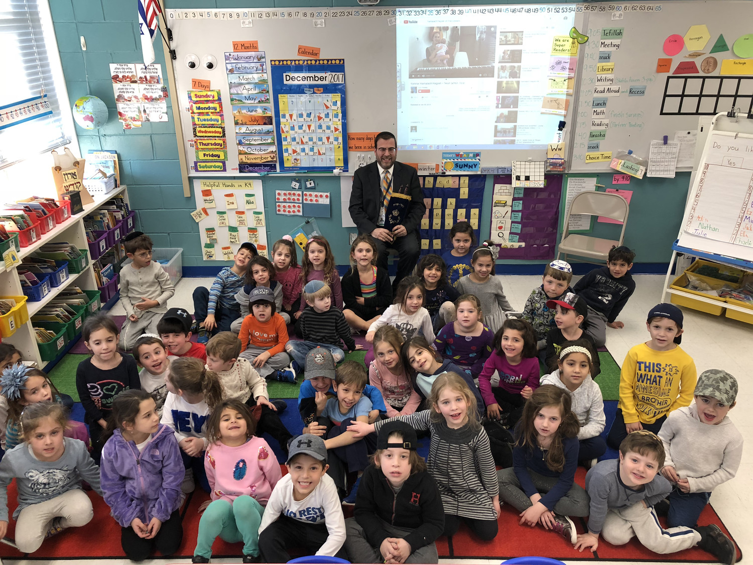 Rabbi Dovid Kupchik, HAFTR's Judaic studies supervisor, with kindergarten students who completed reading the first book of the Old Testament.