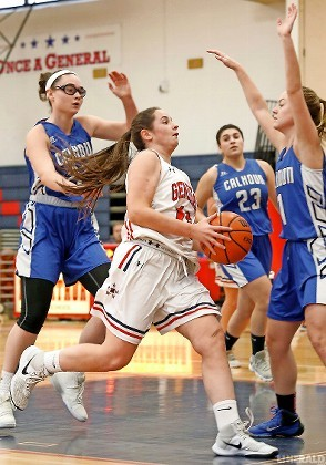 MacArthur's Mackenzie Tierney, center, who scored 10 points despite foul trouble, drove the lane during Monday's 51-41 defeat to Conference AA/A-III rival Calhoun.