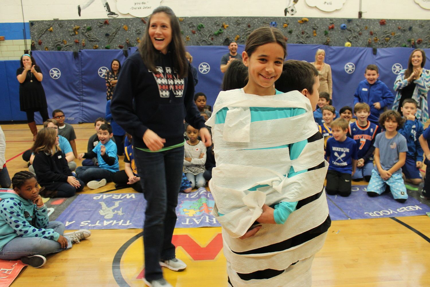 Fifth-grade teacher Andrea Grubb wrapped up Ella Santos and two of her classmates. This group won the toilet paper wrap-up competition.