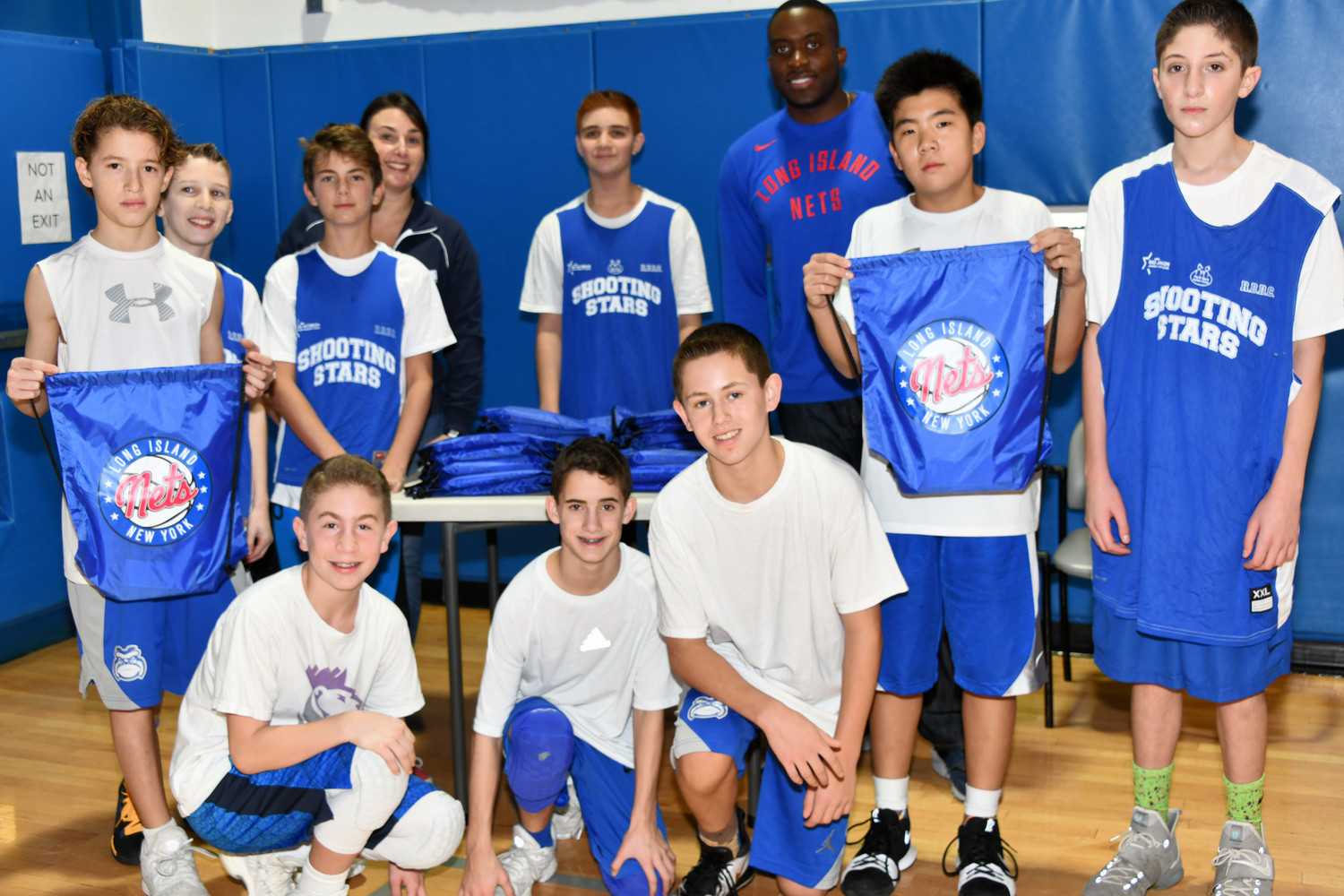 Rachel Gillman, back left, invited Marcon Clarke, third from right, to attend Hoops for Harrison. Clarke is in charge of customer relations for the Long Island Nets.