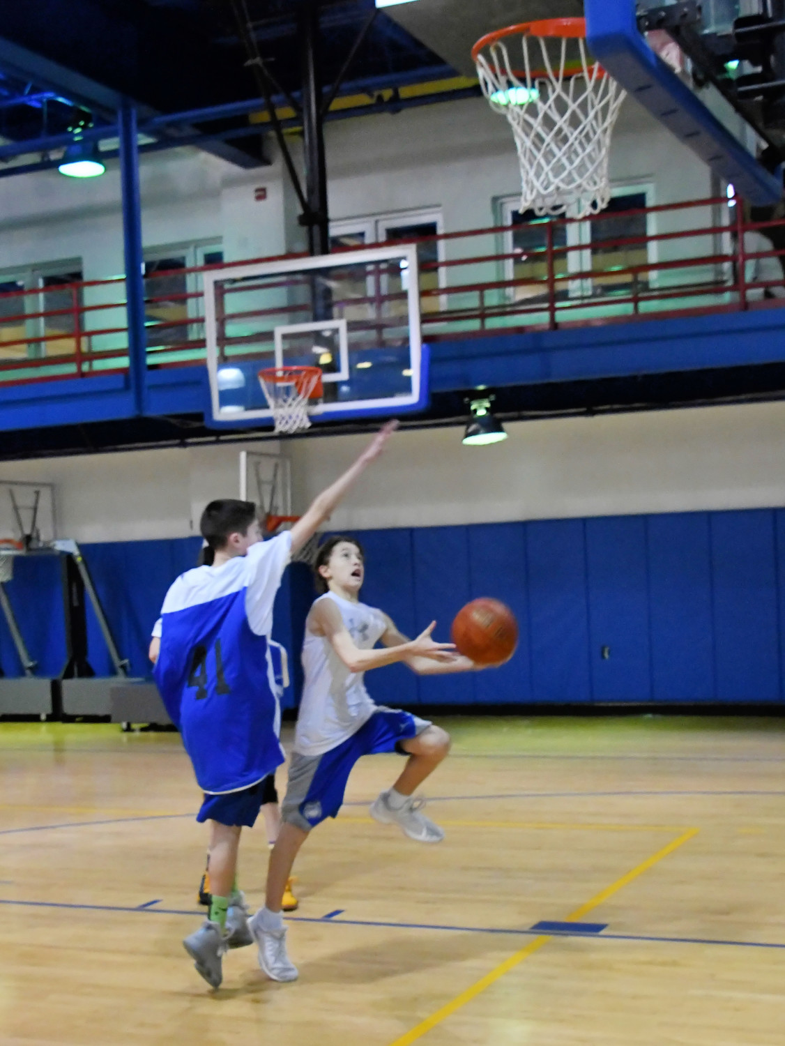 During the middle school game, a player moved in for a layup shot.