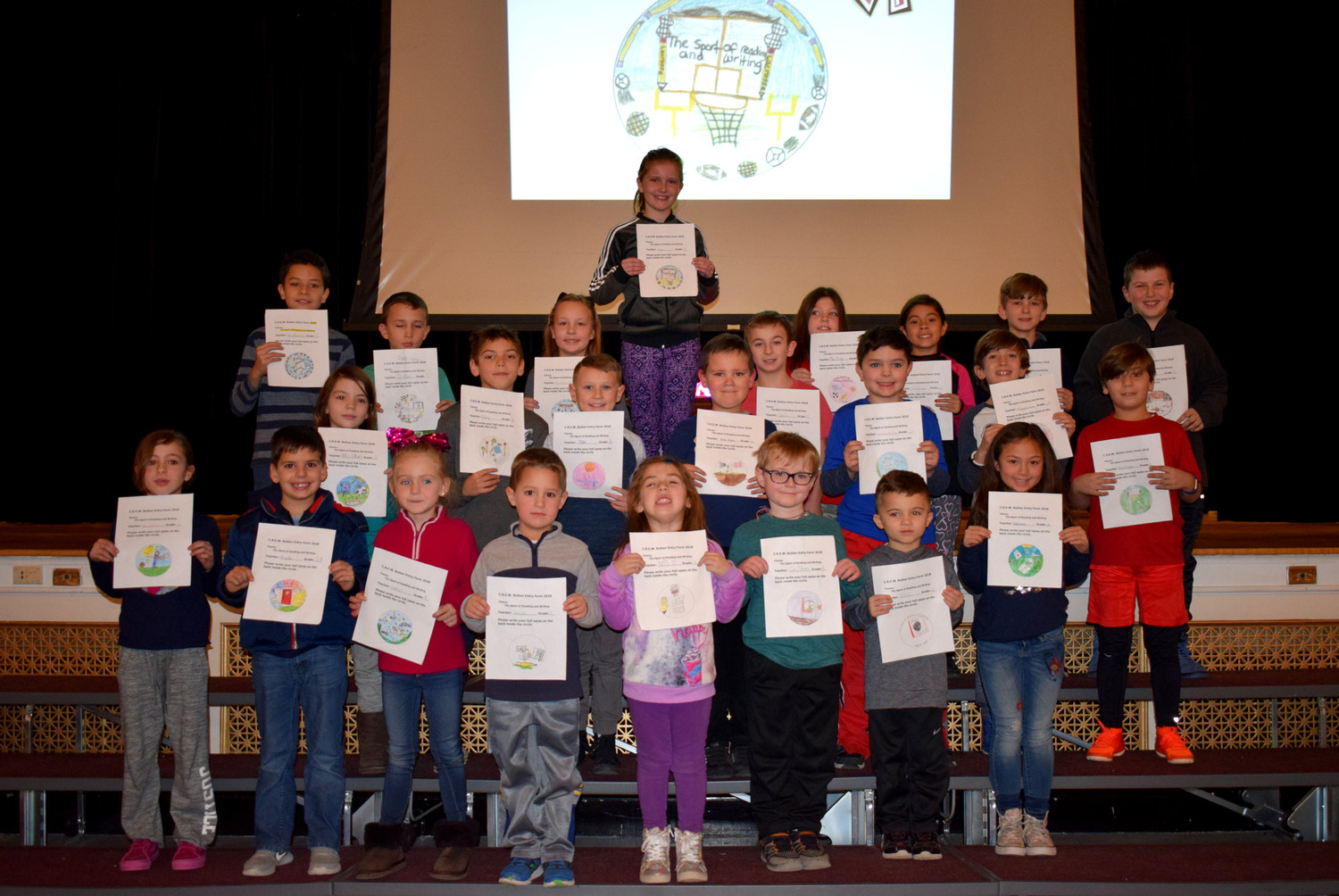 Students participated in drawing the new C.R.E.W. button. During the opening ceremony, the best student buttons from each grade were selected, and the children were called up onstage. The 2018 button contest winner was Avery Fitzpatrick.