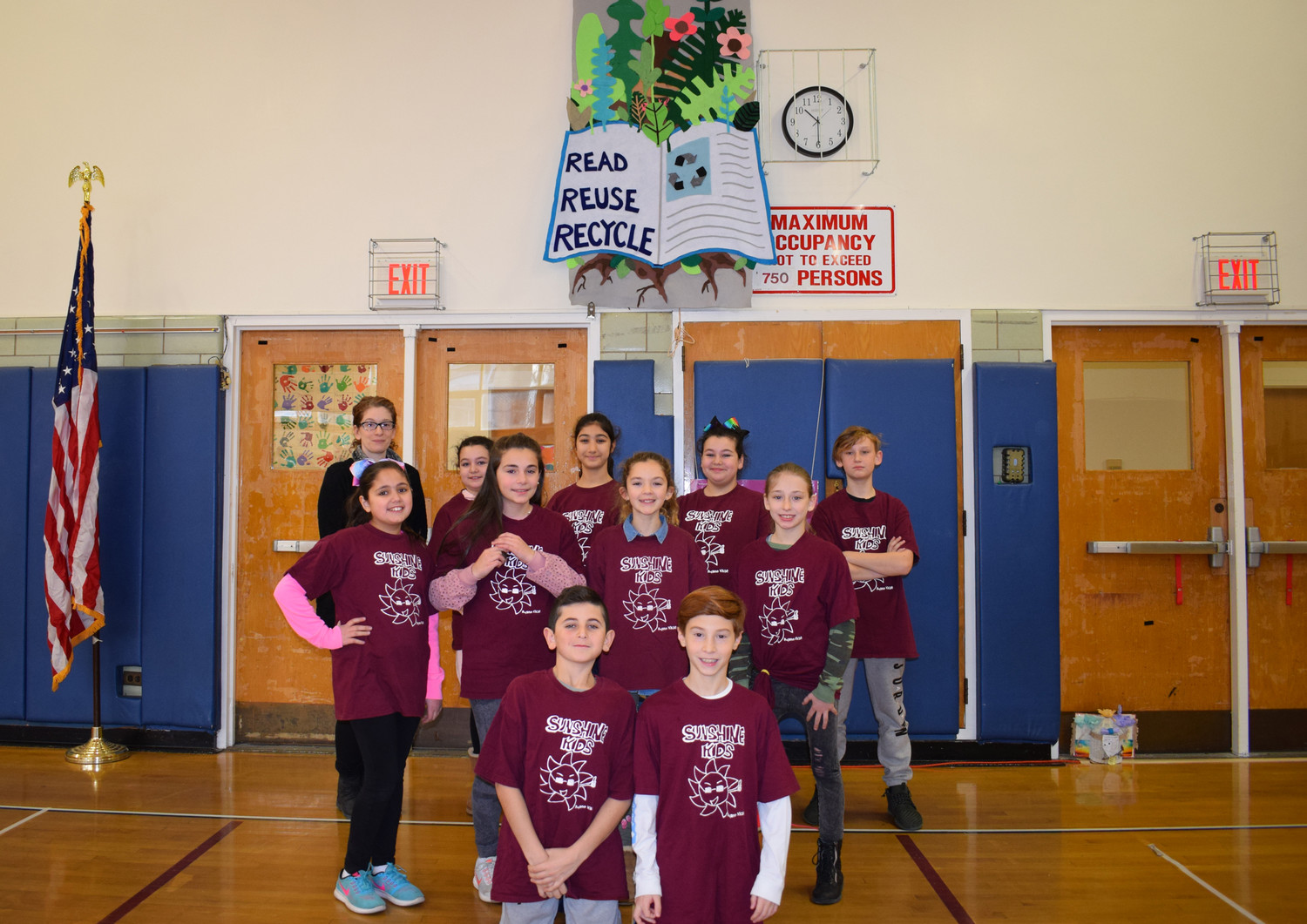 Glen Head School's art club stood proudly with their banner, which they created for the celebration.
