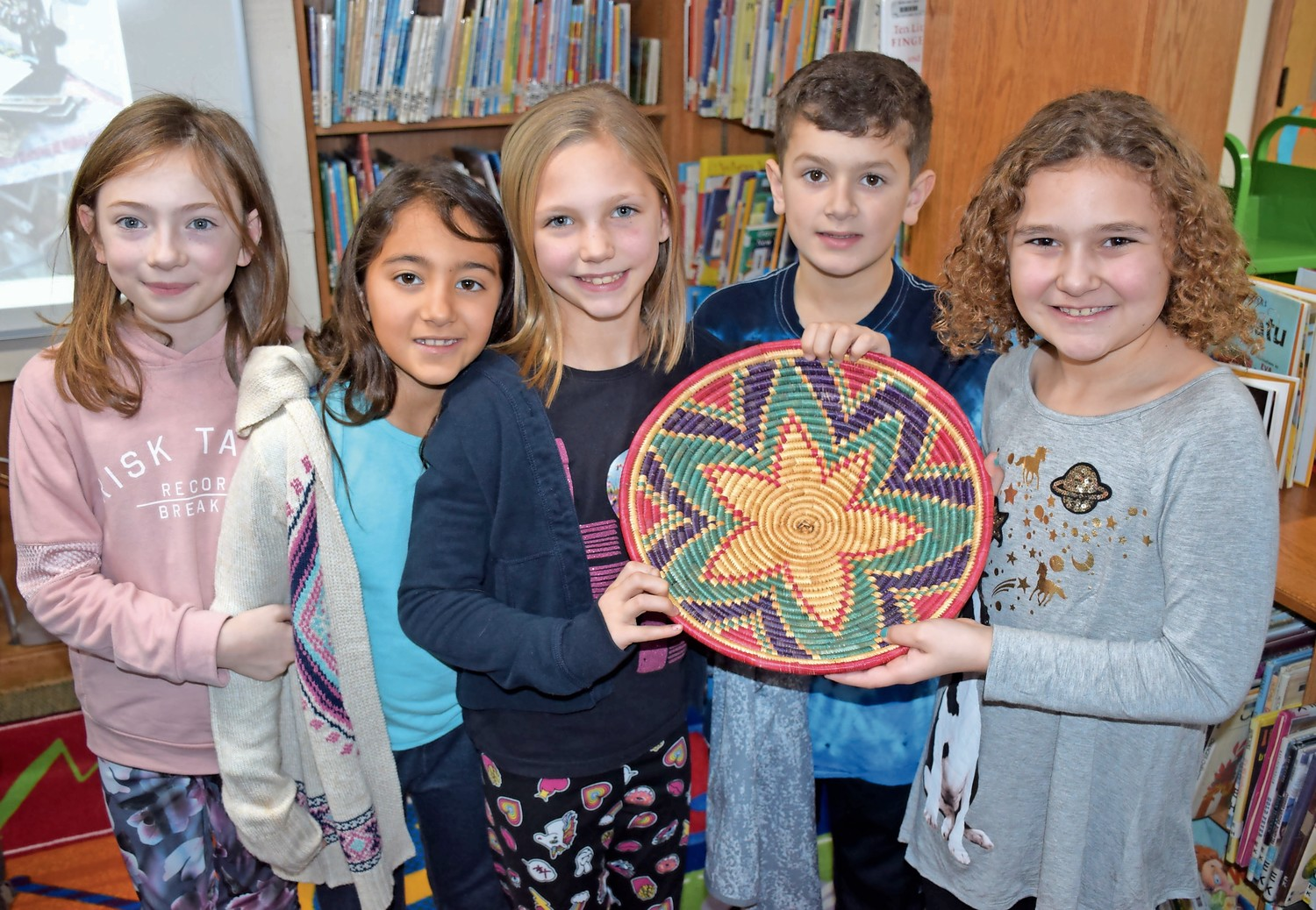 Third-graders, from left, Ciara Foote, Katharyn Malone, Juliet Stebner, Ryan Burke and Erica Simone observed an authentic basket from Kenya.