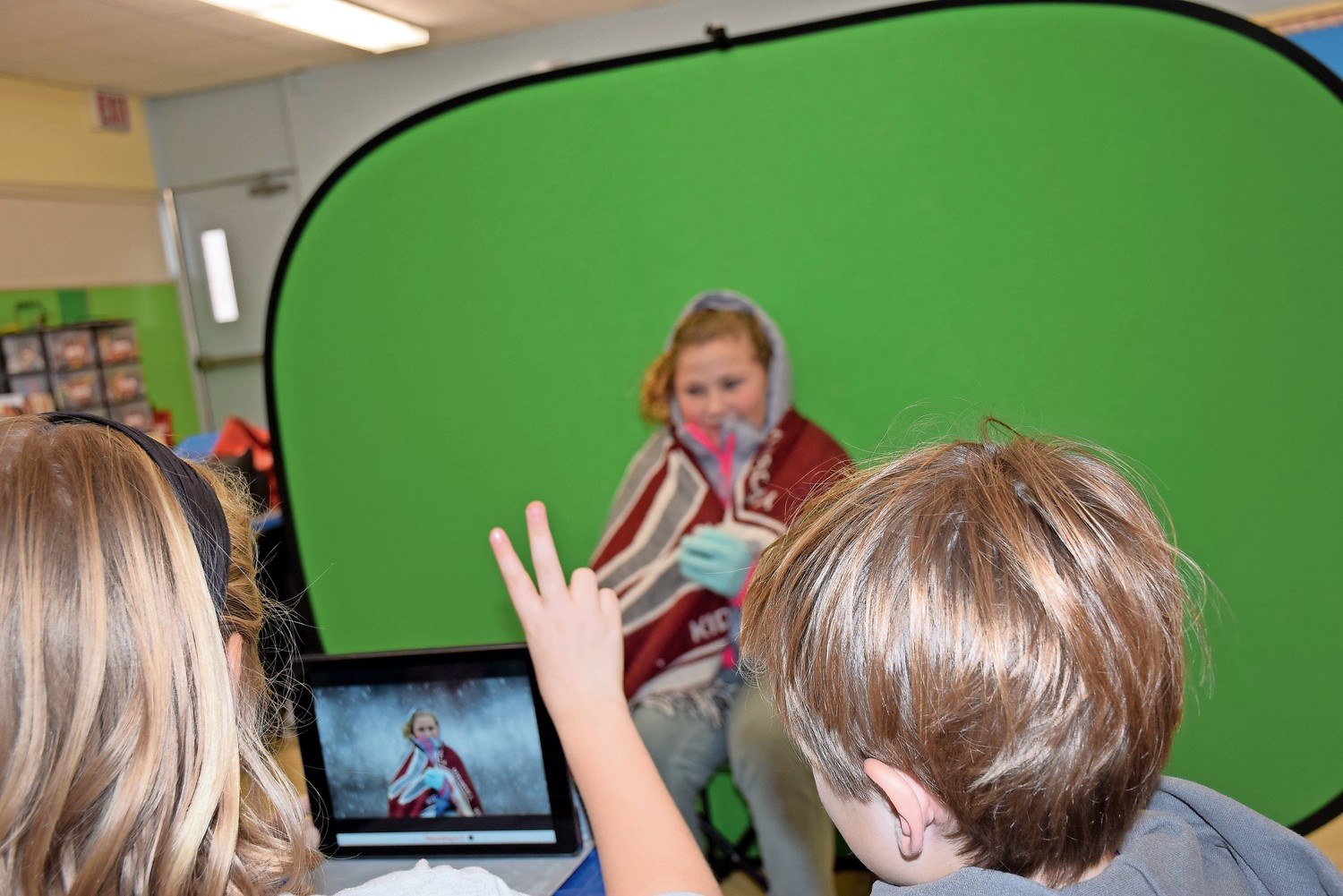 Weather station director Elizabeth Kirchner and anchor Owen Stachlik, directed meteorologist field reporter Jamielynn Korotke in the filming of a weather report at Forest Lake Elementary School.