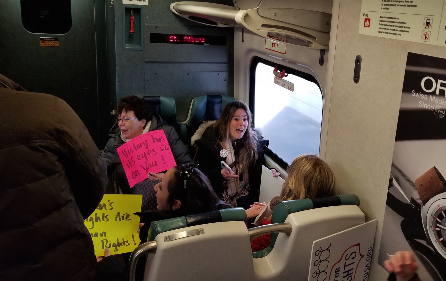Sheila McDougal brandished her Women's March poster with Jamie Jordan, one of the co-founders of RVC Indivisible, as they rode the Long Island Rail Road into New York City.