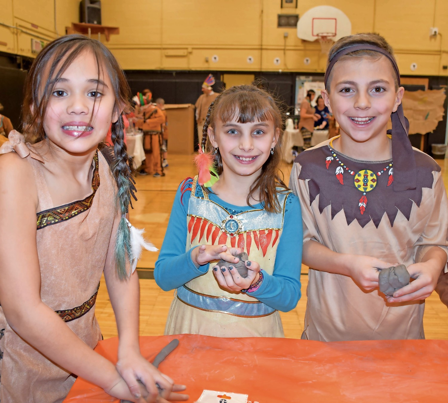 Forest Lake Elementary School students, from left, Madeline Gonzales, Faith Stallone and Colin Calabro crafted clay pots during Native American Day.