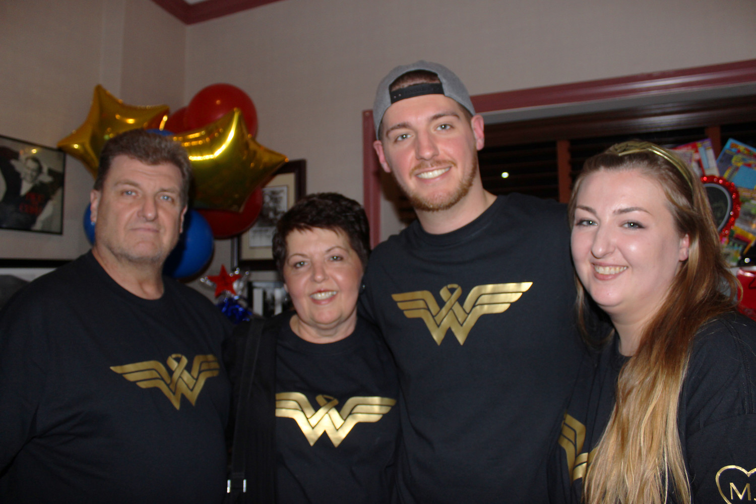 "Millie Jones is often referred to by friends and family as ""Wonder Woman"" because of her dedication to philanthropy and the East Meadow community, and her tenacity in fighting pancreatic cancer, which she was  diagnosed with last March. She was pictured here with her husband, left, and her children Matthew, 24, and Cassandra, 31."
