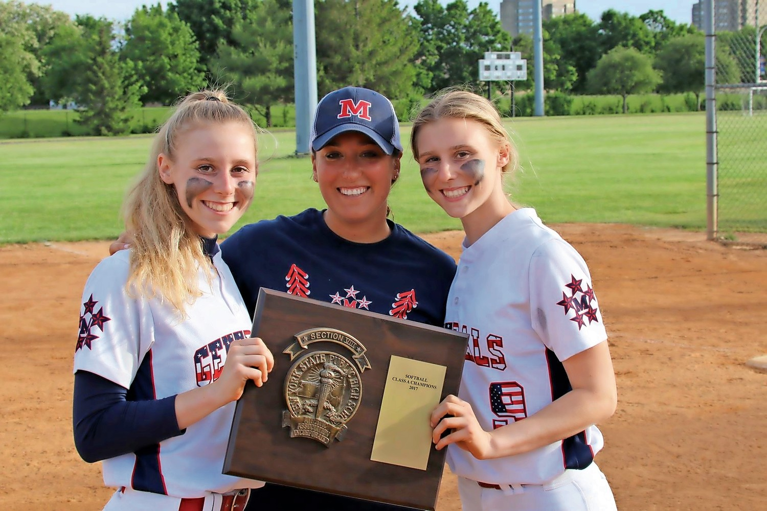 Ashley Budrewicz, left, her sister, Jessica, right, and MacArthur High School assistant softball coach Deana Tororici, center, celebrated their win in the Nassau County Softball Division A Championship series last May.