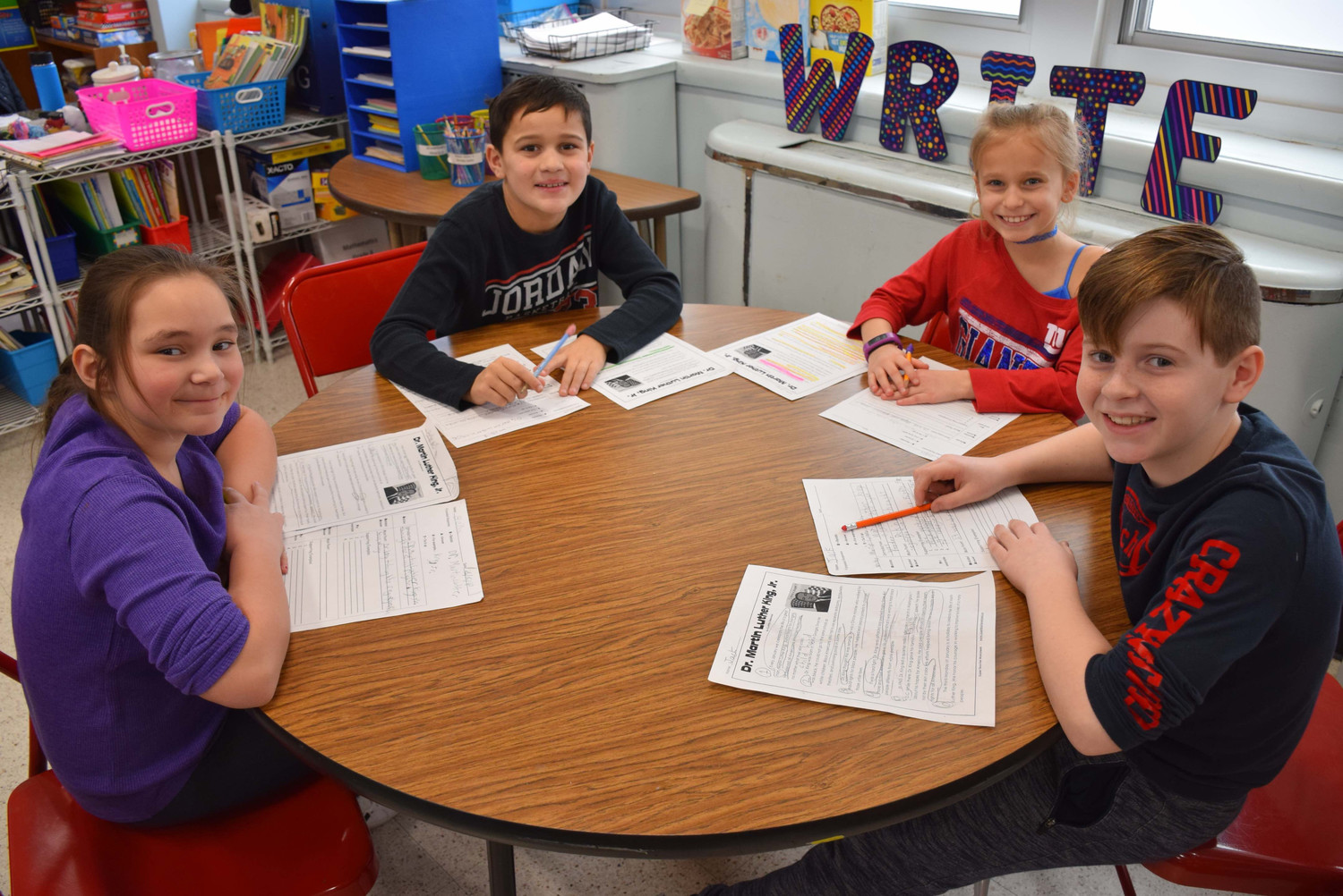 John Dinkelmeyer Elementary School fourth-graders Bella Wunner, left, Lucas Paingankar, Jordyn Dioguardi and Jack Weber completed response sheets after reading about Dr. Martin Luther King Jr.