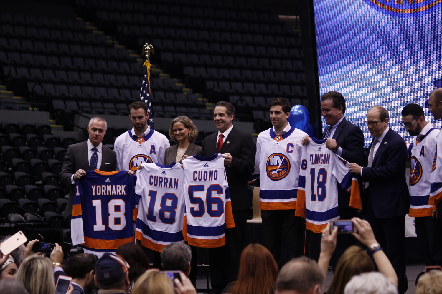 Brett Yormark, the CEO of Brooklyn Sports & Entertainment, left, County Executive Laura Curran, Gov. Andrew Cuomo and Senate Majority Leader John Flanagan were given honorary Islanders jerseys in honor of the team's return to Long Island. They were accompanied by Islanders co-owner Jon Ledecky and several players.
