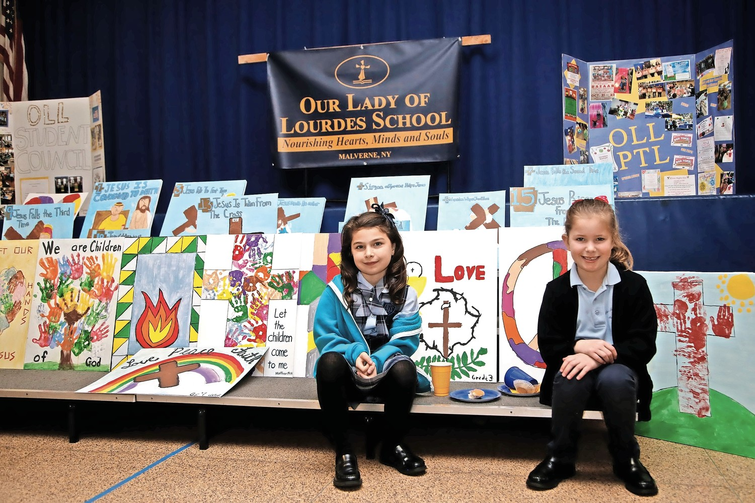 Second-graders Allison Connolly, left, and Katherine Frohme take a break from the festivities at O.L.L.