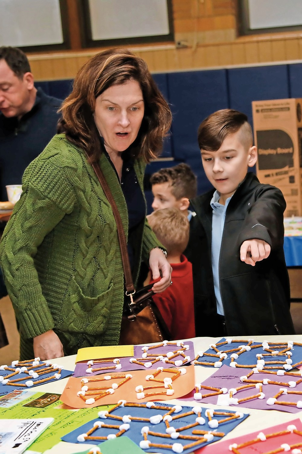 Fouth-grader Aidan Miller points out his marshmallow-pretzel geometric shapes project to his mother Sandy.