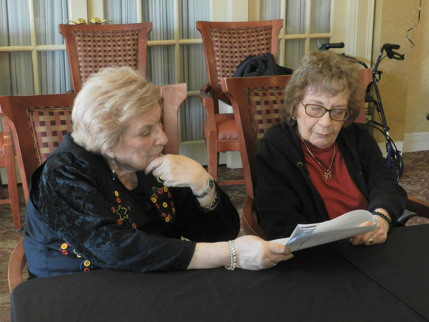 Evelyn Floresta, left, and Claire Margolis, followed along with the prayer book provided to guests at the Tu B'Shevat seder.