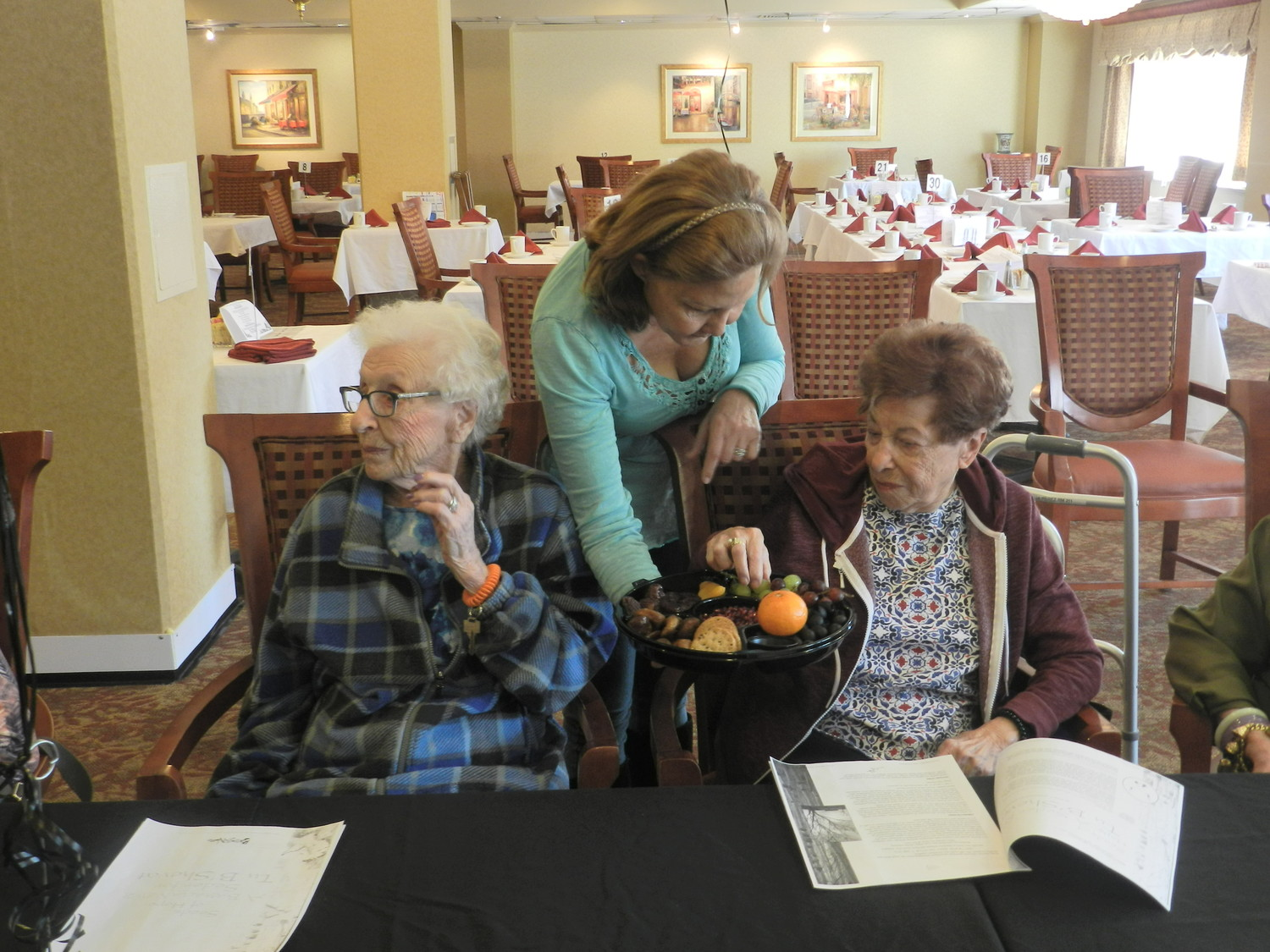 Victoria Wexler, offered resident Marie Galluccio a plate full of fruits and grains that symbolized the harvests of Tu B'Shevat.