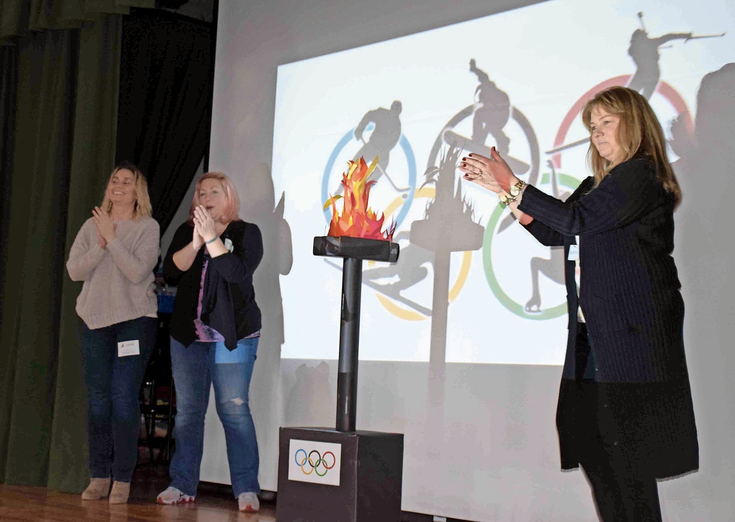 Principal Debra Emmerich, right, and PTA Co-Presidents Lacey Redlefsen and Jessica Schlitter placed the Olympic torch.