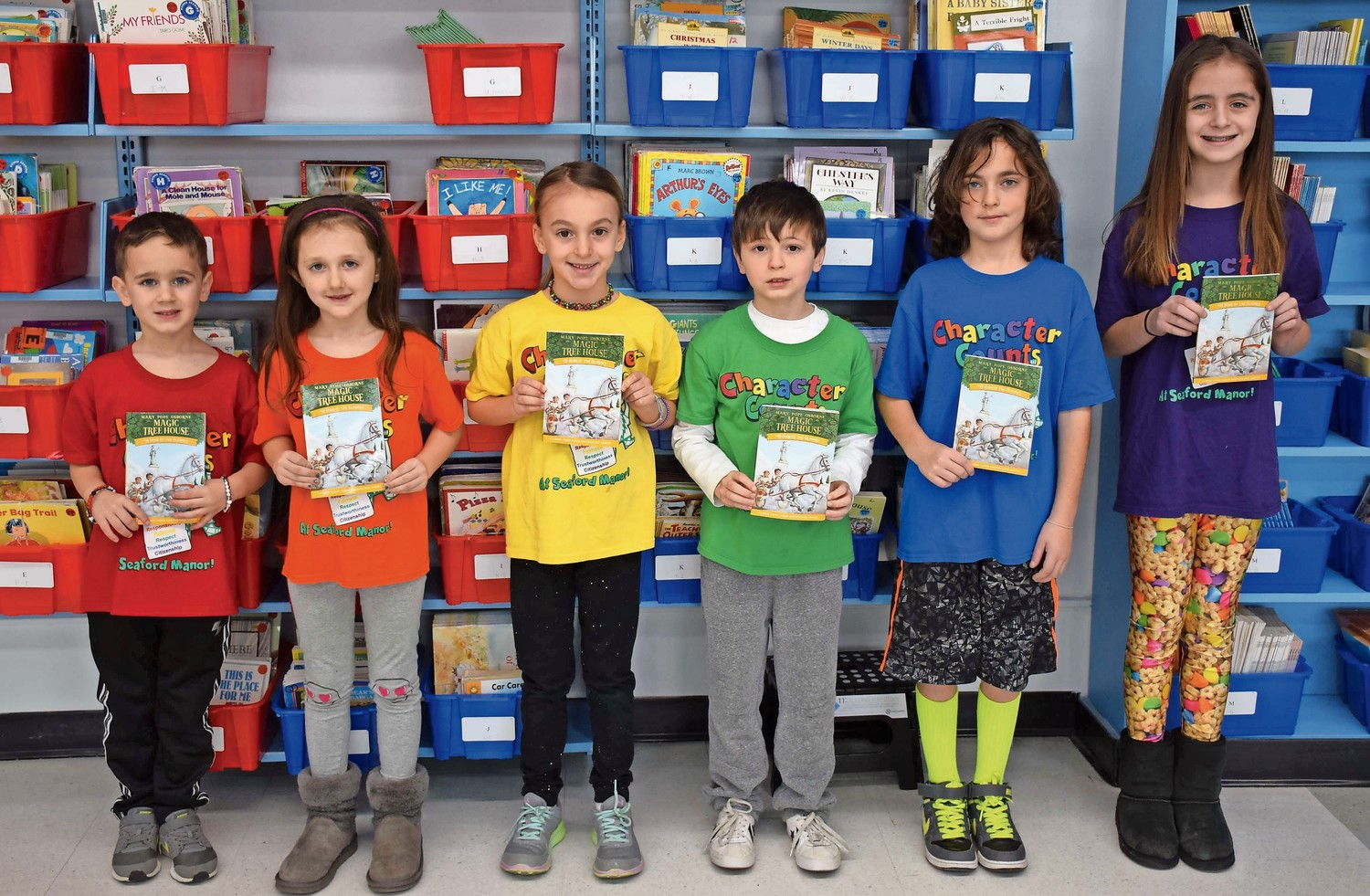 "Seaford Manor Elementary School students, from left, kindergartner Max O'Hagan, first-grader Hailey Salamon, second-grader Serena D'Amato, third-grader Ethan Arahovites, fourth-grader Frankie Padavan and fifth-grader Alaina Reid received copies of ""Hour of the Olympics,"" which all students will read for the Pick A Reading Partners program."