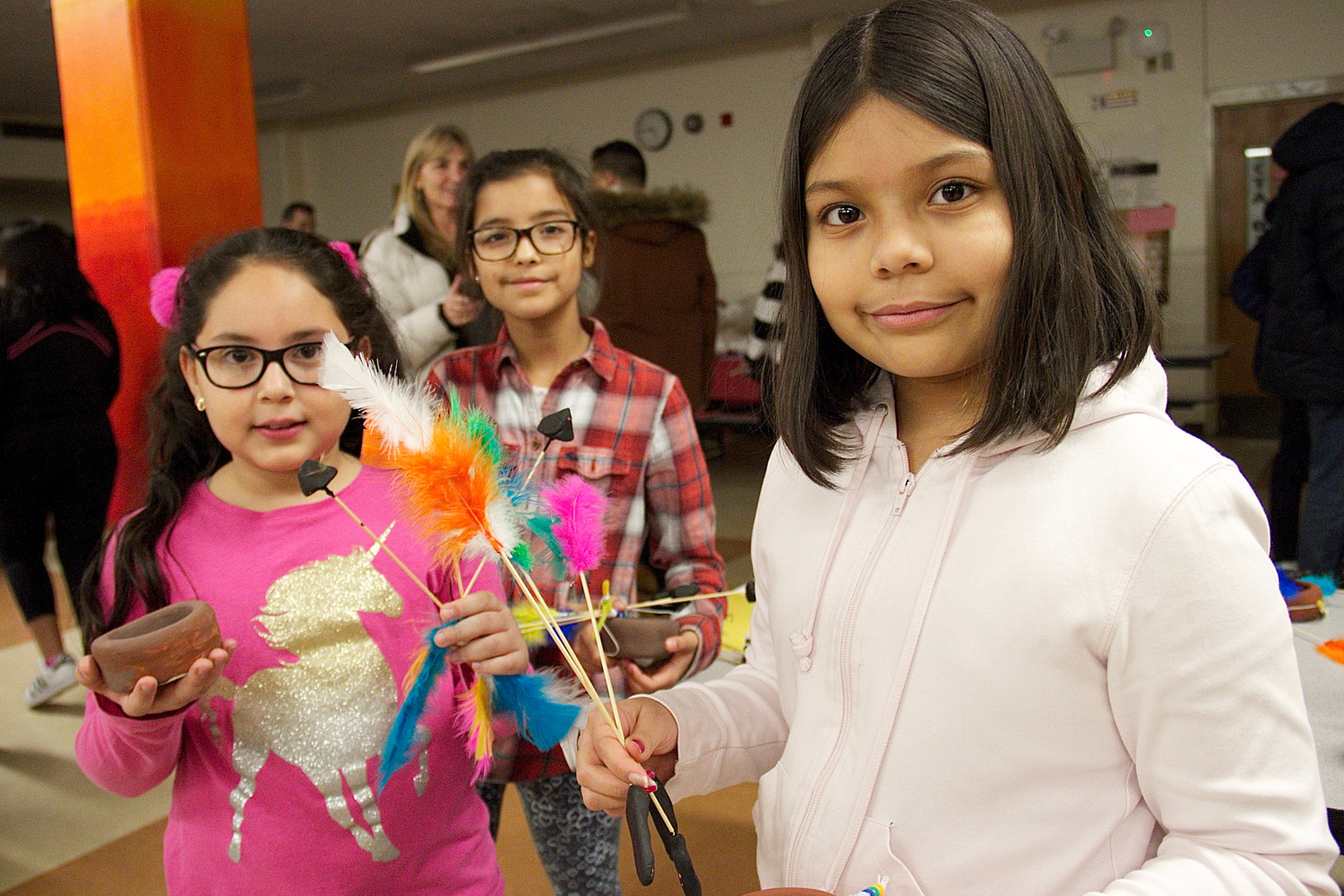 "Fourth-grader Daniella Mendoza, top left, and fifth-graders Hannah Gansky, and Delaila Majano showed off the crafts they made for the art show, ""Through the Ages."""