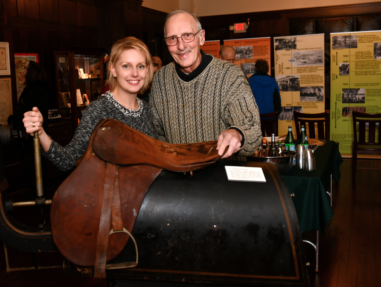 "Museum director Amy Driscoll demonstrates a 19th century ""Zander Horse Exerciser,"" a piece of winter exercise equipment with Dave DeRiggi."