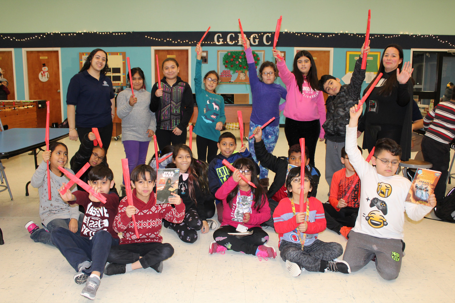 The kids of the Glen Cove Boys and Girls Club showed off their lightsaber skills with Jacqueline Telleria, the program director.