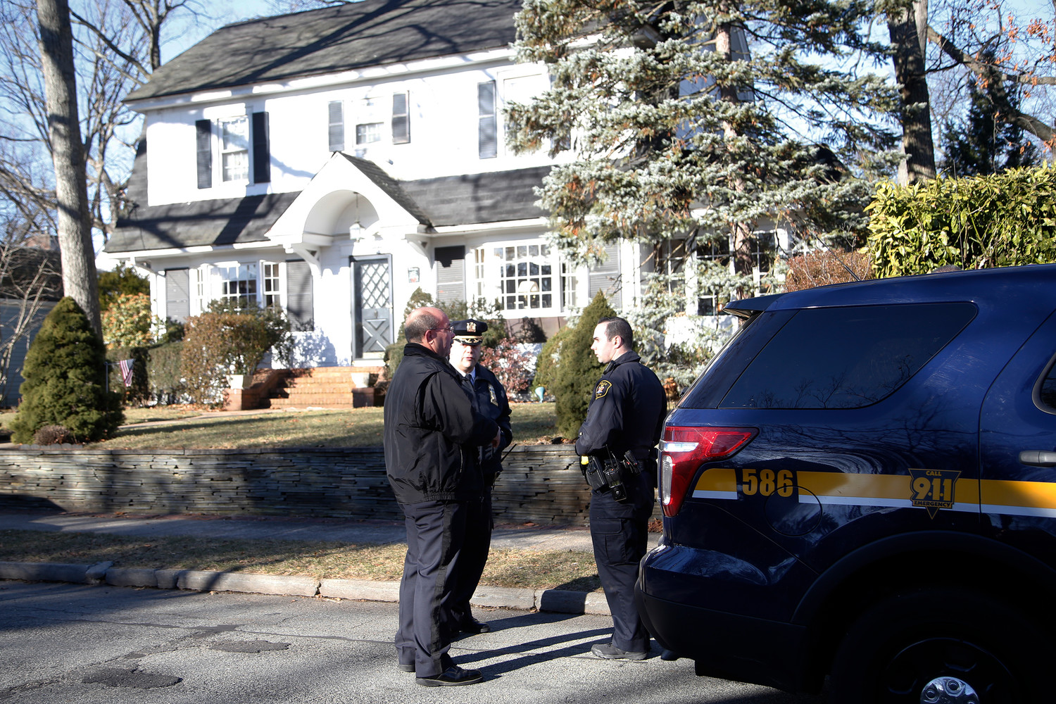 Malverne Police Department Chief John Aresta and officers in front of the house where Joseph Barbella was found early Tuesday morning.