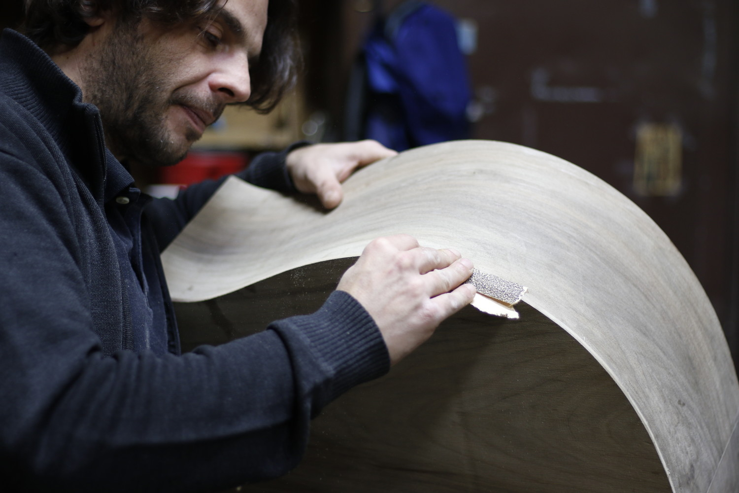 After assembling the body of a bass, Simone Diana, who is originally from Italy, sanded the willow bark to smooth out the edges.