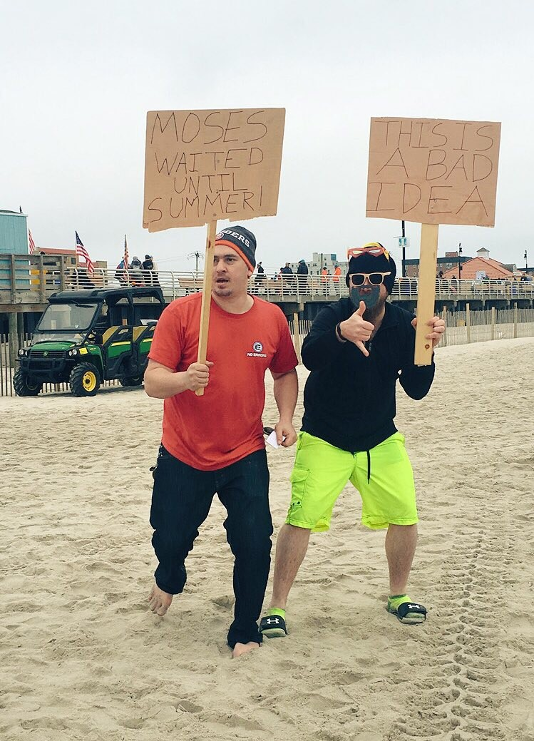 James DeNatale, left, and Richard McWilliams displayed signs at the plunge that jokingly discouraged people from running into the water. While some onlookers were offended, they said, most people laughed. The pair supports the cause, and took the plunge themselves.