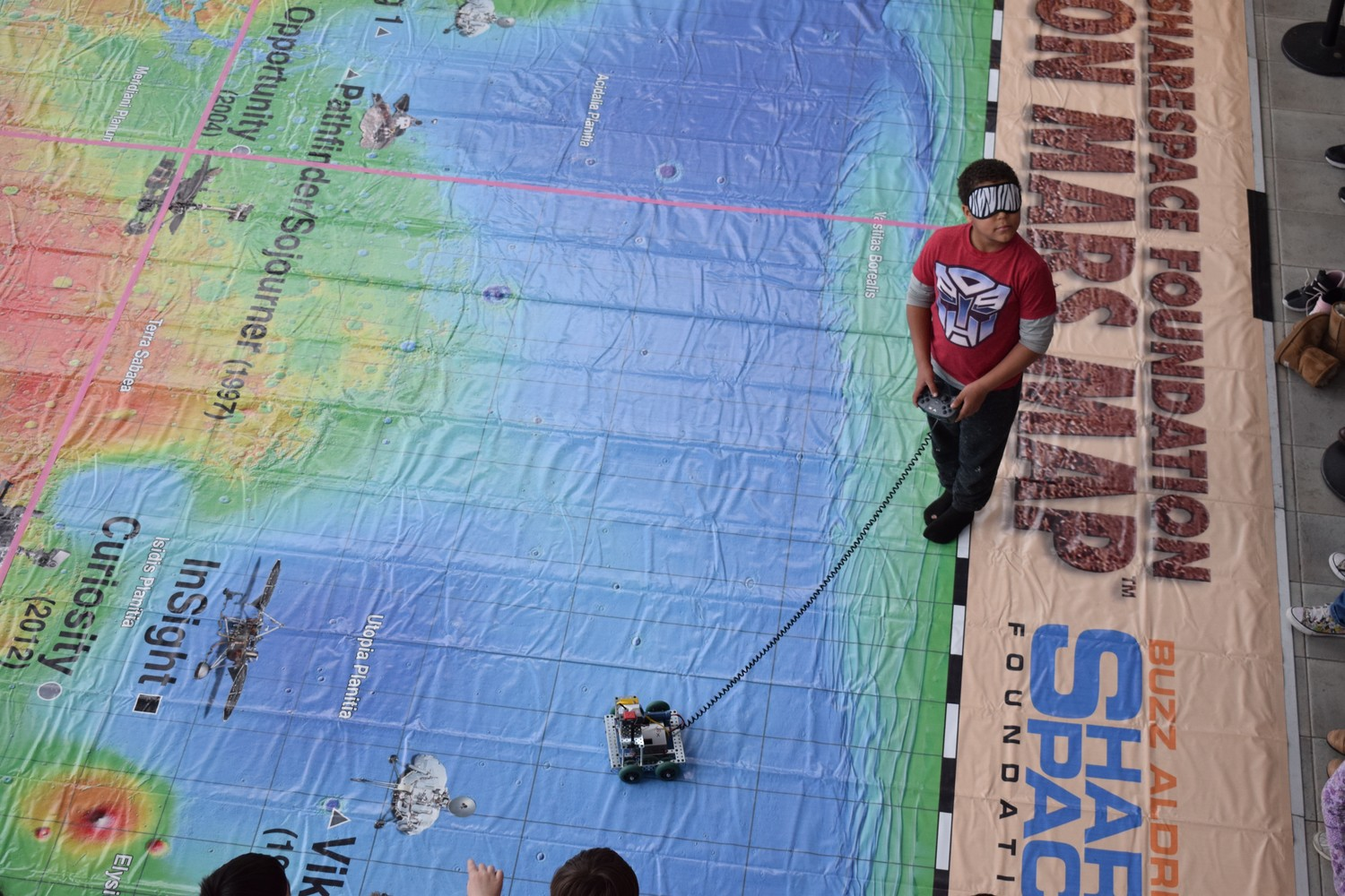 Student tries his 'hand' at handling a miniature rovers on a giant 25-foot x 25-foot vinyl Mars map provided by the Buzz Aldrin Share Space Foundation.